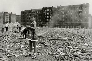 Young girl standing infront of burning blocks in the Bronx
