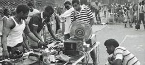 Young Black kids gathered around DJ decks at a block party